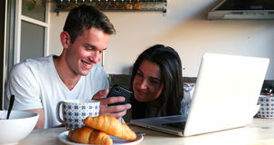 Couple using mobile phone and laptop while having breakfast. In kitchen stock footage