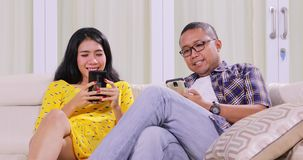 Couple using mobile phone in living room. Two young couple using mobile phone together while relaxing on the sofa in the living room at home. Shot in 4k stock video