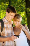 Couple using mobile phone outdoors Stock Photography