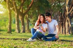 Couple using mobile phone in park. Couple using mobile phone in the park Stock Image