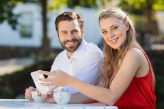 Couple using mobile phone in a restaurant. Happy couple using mobile phone in a restaurant Stock Photo