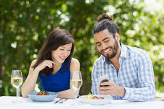 Couple using mobile phone in a restaurant. Happy couple using mobile phone in a restaurant Royalty Free Stock Photo
