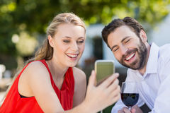 Couple using mobile phone in a restaurant. Happy couple using mobile phone in a restaurant Stock Image