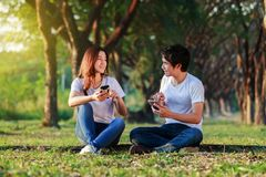 Couple using mobile phone and talking in park. Couple using mobile phone and talking in the park Stock Photography