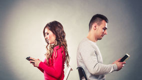 Couple using mobile phones not talking. Conflict. Royalty Free Stock Photography