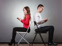 Couple using mobile phones not talking. Conflict. Stock Photo