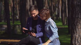 Couple using modern device and laughing outdoor. stock footage