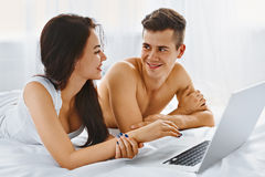 Couple using notebook on bed Royalty Free Stock Image