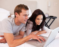 Couple using notebook together in the bedroom Stock Photos