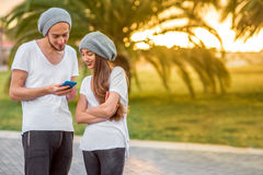 Couple using phone in the park Stock Image