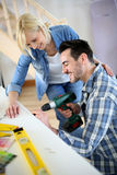 Couple using  power drill for woks in house Royalty Free Stock Photos