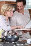 Couple using a recipe book. Couple following a recipe from a book Royalty Free Stock Photos