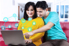 Couple using smart home controller on laptop Stock Photos