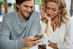 Couple using smart phone at table in coffee shop Royalty Free Stock Photo