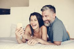 Couple using a smartphone in bed royalty free stock photos