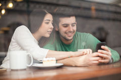Couple using a smartphone in a coffee shop. Attractive young couple looking at a photo in a smartphone while having some coffee in a restaurant Royalty Free Stock Image
