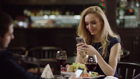 Couple using smartphone during dating in cafe. Pair with phones at dating in restaurant. lovers with mobiles dating stock footage