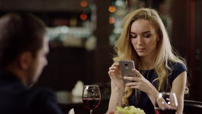 Couple using smartphone during dating in pompous cafe. Pair using smartphone during dating in restaurant stock video footage