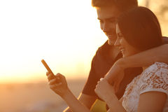 Couple using a smartphone in a sunset back light Royalty Free Stock Images