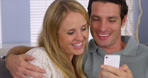 Couple using smartphone to video chat with family Stock Image