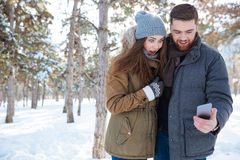 Couple using smartphone in winter park Royalty Free Stock Photography