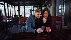 Couple using smartphones to choose place for rest in summer. Couple using smartphones to choose place for rest summer, young people sitting near table in coffee stock video