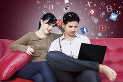 Couple using social network with laptop on sofa Stock Images