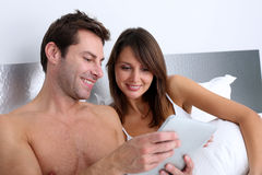 Couple using tablet in bed Stock Photography