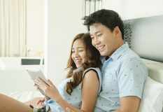 Couple Using Tablet On The Bed Royalty Free Stock Photo