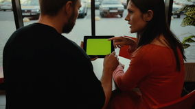 Couple using tablet computer in cafe. green screen. Young couple, man and  woman, using digital tablet computer in cafe. green screen stock footage