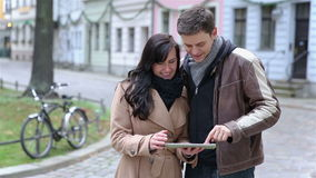 Couple using tablet computer in city Stock Photography