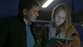 Couple using tablet computer on flat escalator. Young man and woman riding on flat escalator in underground and using touch pad. They discussing something shown stock footage