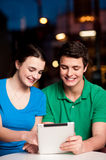 Couple using tablet computer at an outdoor cafe Royalty Free Stock Image