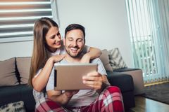 Couple using a tablet online sitting in the living room at home stock image