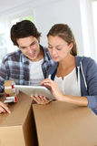 Couple using tablet while packing Stock Images
