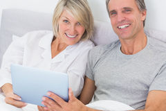 Couple using tablet pc in bed smiling at camera Stock Photos