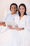 Couple using tablet pc in their bed Royalty Free Stock Image
