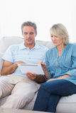 Couple using tablet pc together on the sofa Stock Photos
