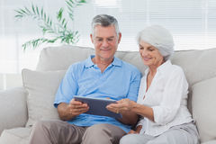 Couple using a tablet sitting on the couch Stock Photo