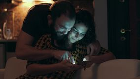 Couple using tablet on sofa at night in room stock footage