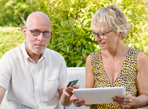 Couple using tablet to make a purchase,. Senior couple using tablet to make a purchase stock image