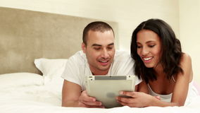 Couple using tablet together in bed stock video footage