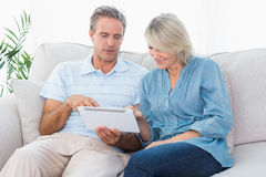 Couple using tablet together on the sofa Royalty Free Stock Photography