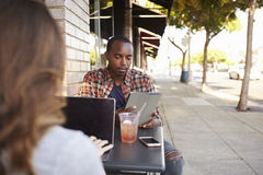 Couple using technology at a table outside a cafe Royalty Free Stock Photos