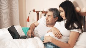 Husband and pregnant wife using their laptop in the bed stock video footage