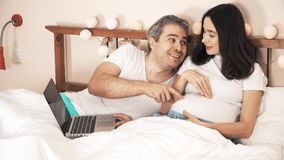 Husband and pregnant wife shopping online in the bed royalty free stock images