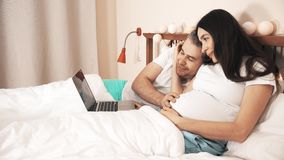 Man and his beautiful pregnant wife using their laptop in their bed stock footage