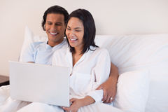 Couple using their laptop while sitting on the bed Royalty Free Stock Image