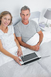 Couple using their laptop together in bed Royalty Free Stock Photos
