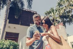 Couple using their phone while on vacation stock photography